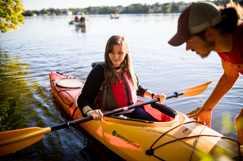 A member of the Buccaneer Boathouse group assists other students in experiencing paddle sports on...