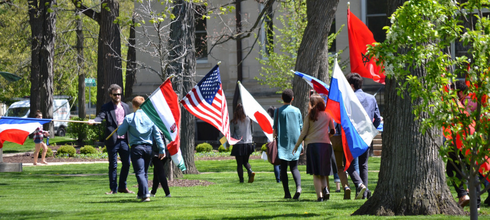 A group of international students walking along the lawn outside of Middle College, waving flags ...