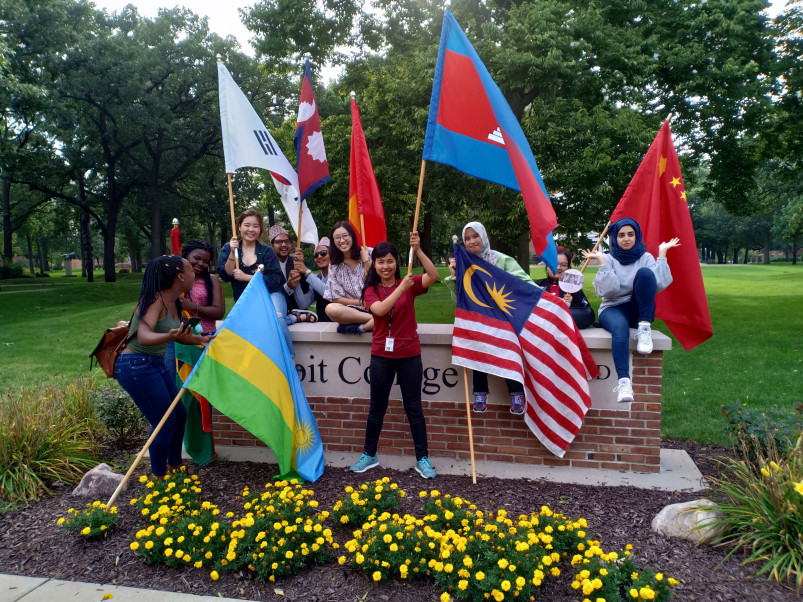 International students wave their flags in front of the Beloit College sign following Convocation...