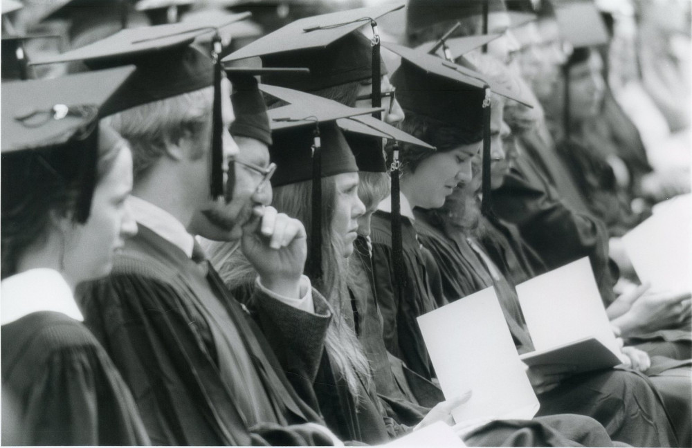 Students seated with their diplomas during commencement, circa 1980.