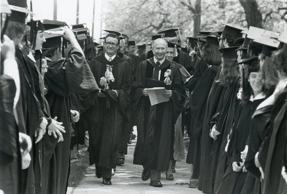 Faculty process through lines of students before commencement, circa 1981.