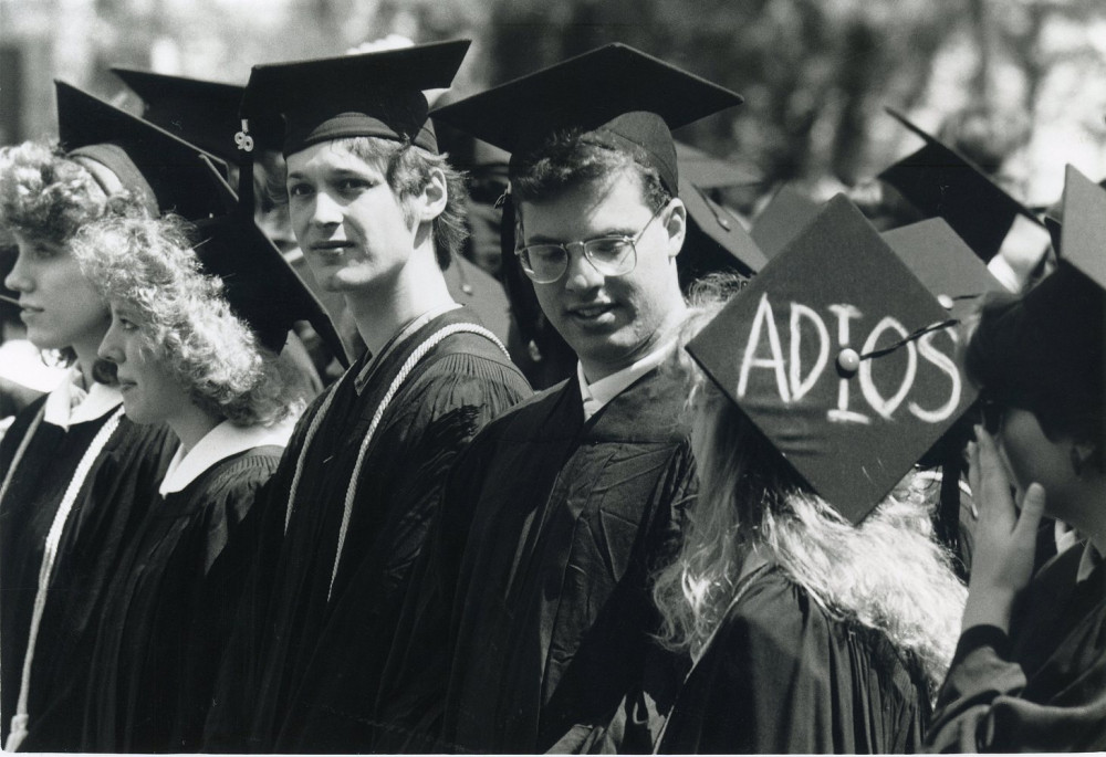 Students talking during the commencement ceremony, one with a cap reading ?Adios?, circa 1990.
