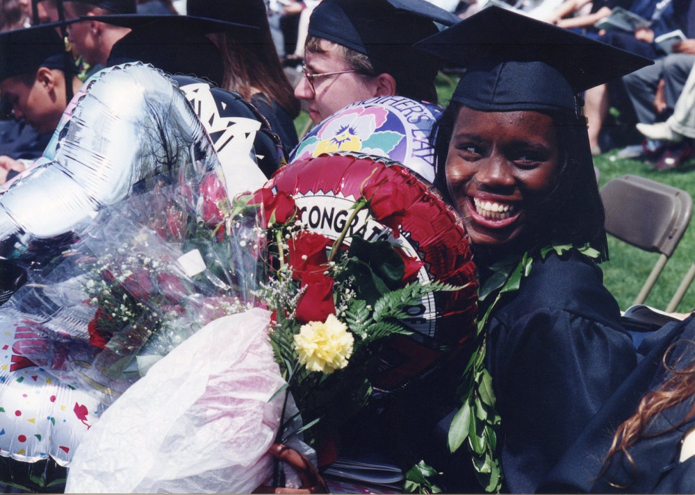 "A smiling student buried in flowers and balloons reading ""congratulations"", circa 1997"