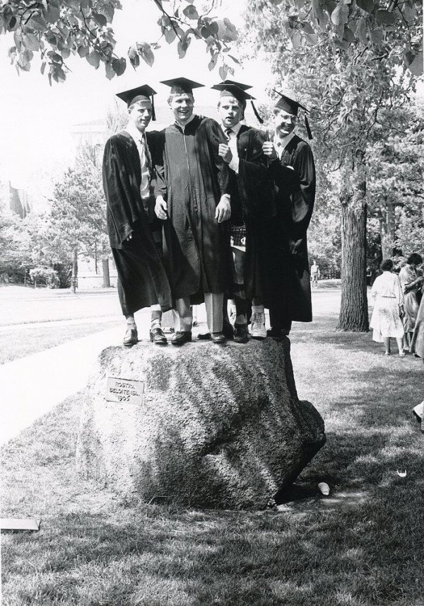 Four students stand on together on the rostra rock, circa 1987.