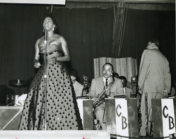 Sarah Vaughn performs in the Field House as Count Basie and his orchestra look on.