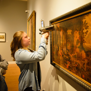 Chemistry major Sarah Farr'19 analyzes the painting Venus at the Forge of Vulcan with a handheld X-ray fluorescence spectrometer in the Wright Museum of Art.
