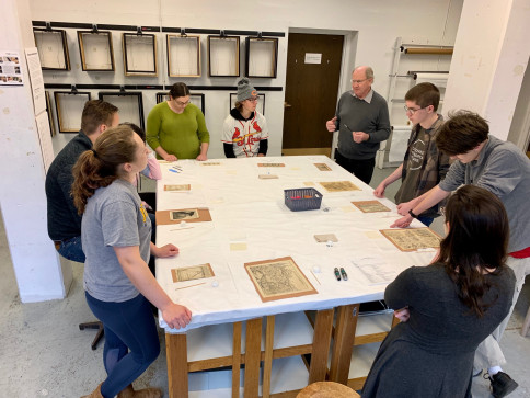 Introduction to Collections Management students learn from Jim DeYoung how to remove prints from ...