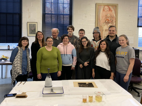 Group photo with the washed print on the table. The cups of yellow water in the foreground hold w...