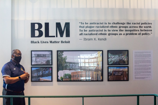 Dean of Students Cecil Youngblood stands in front of the new BLM photo gallery display.