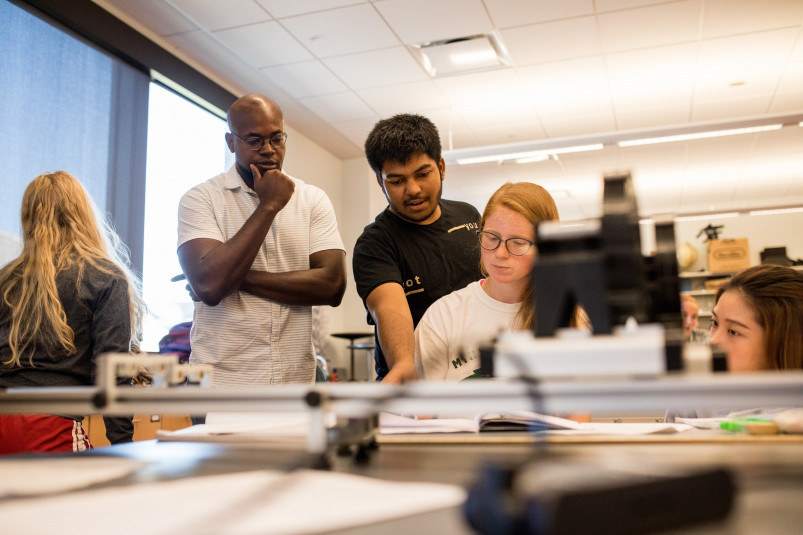 Physics Professor Obioma Ohia observes students as they discuss a class project.