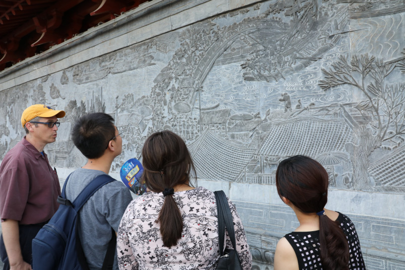 Professors and students study a relief panel in the Yellow river area of China during the Landsca...