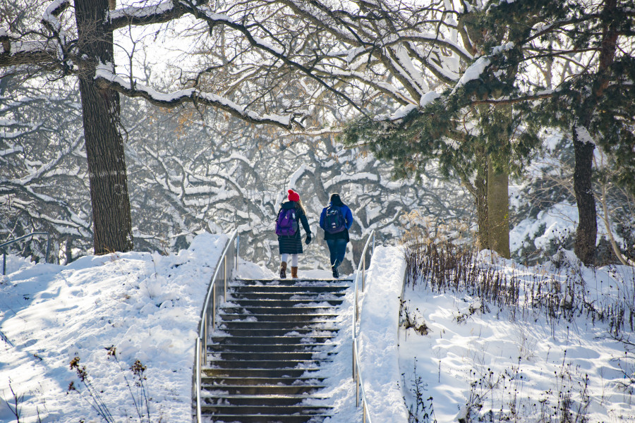 Two students ascend a snow covered stairway on the Beloit College campus.