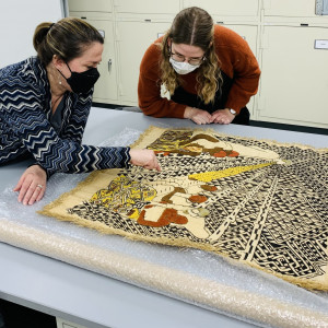 Nicolette Meister, Logan Museum Director, and Celia Edwards, exchange student from York University, examine a contemporary Shoowa design cloth from the DRC.