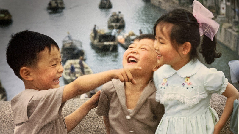 Three Chinese children laughing on a bridge.