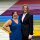 Aimee Oda'16 and Melissa Korniejczuk'17 pose in front of a rainbow wall.