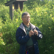 Ken Yasukawa observing birds in the field.