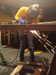 Lydia Sancetta using the plasma cutter to construct a set piece at work.