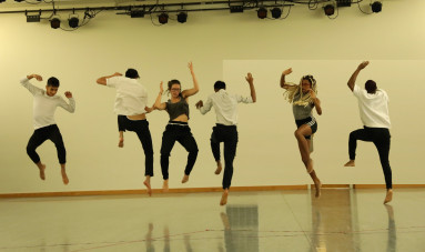 During rehearsal in the new studio students leap to the music.