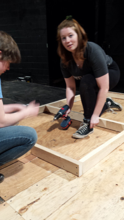 Lemon Wood and Emma Bangs hard at work in the scene shop building the floor for an upcoming show.