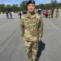 "Xilong ""Tony"" Zhu'13 standing at attention in military garb."