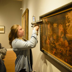 Chemistry major Sarah Farr'19 shoots a handheld X-Ray fluorescence analyzer at a painting in the Wright Museum of Art's permanent collection.