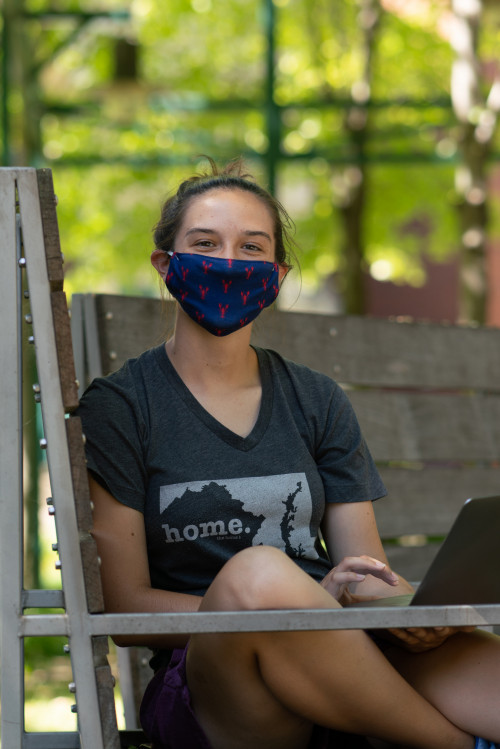 A student working in the Poetry Garden, wearing a mask.