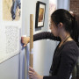 In the Neese Gallery of the Wright Museum of Art, Gaizi Jie'15 installs a propaganda poster featuring Chairman Mao sitting alongside the Yellow River. Gaizi Jie, on an honors term this fall, was participating in an intensive museum studies course called Exhibit Workshop.