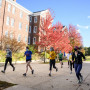 The women's Track and Field team runs behind Wood Hall in autumn.